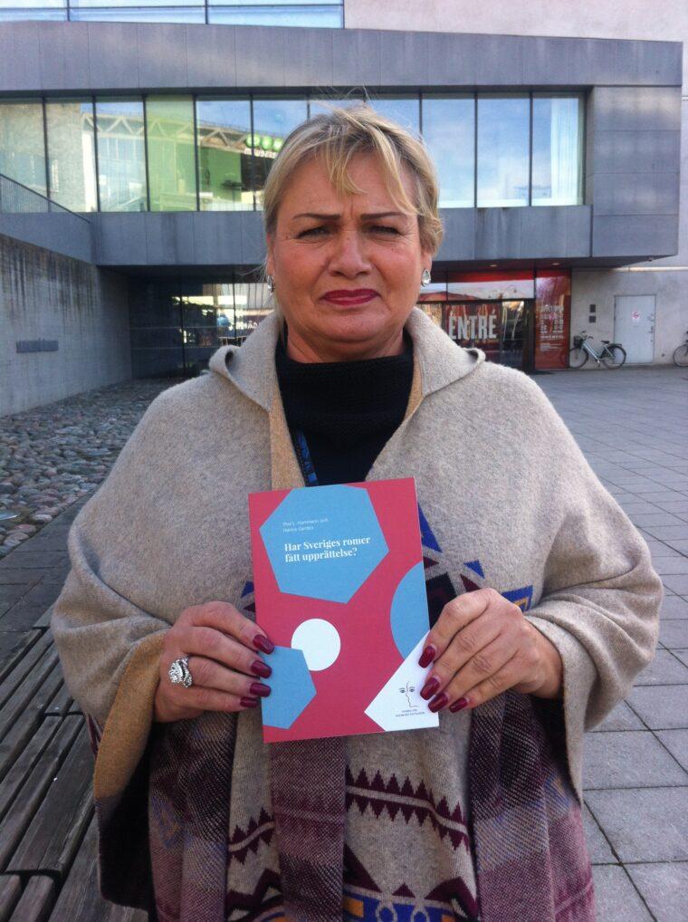 """Bild på Soraya Post, EU-parlamentariker, med MR-Fondens skrift: """"Har Sveriges romer fått upprättelse?"""" från 2015."""